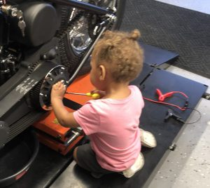 Granddaughter working on the motorcycle.